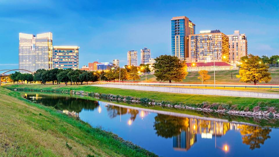 Panoramic photo of the skyline of Fort Worth with apartments and office buildings reflecting in the Clear Fork Trinity River at Trinity Park, in downtown Fort Worth,Texas, USA.