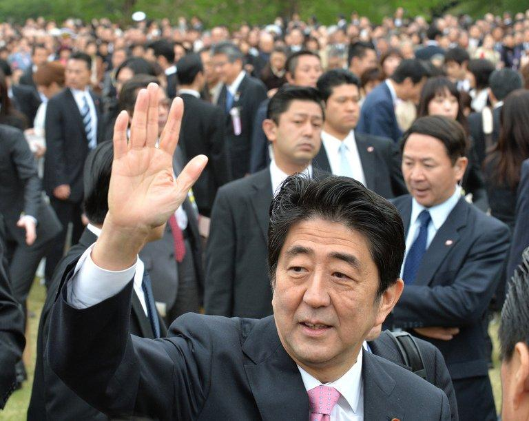 Japan's Prime Minister Shinzo Abe waves to crowds in Tokyo on April 20, 2013