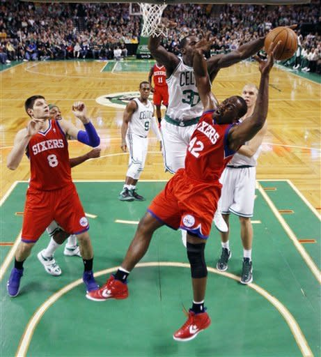 Boston Celtics' Brandon Bass (30) blocks a shot by Philadelphia 76ers' Elton Brand (42) in the first half of an NBA basketball game in Boston, Sunday, April 8, 2012. (AP Photo/Michael Dwyer)