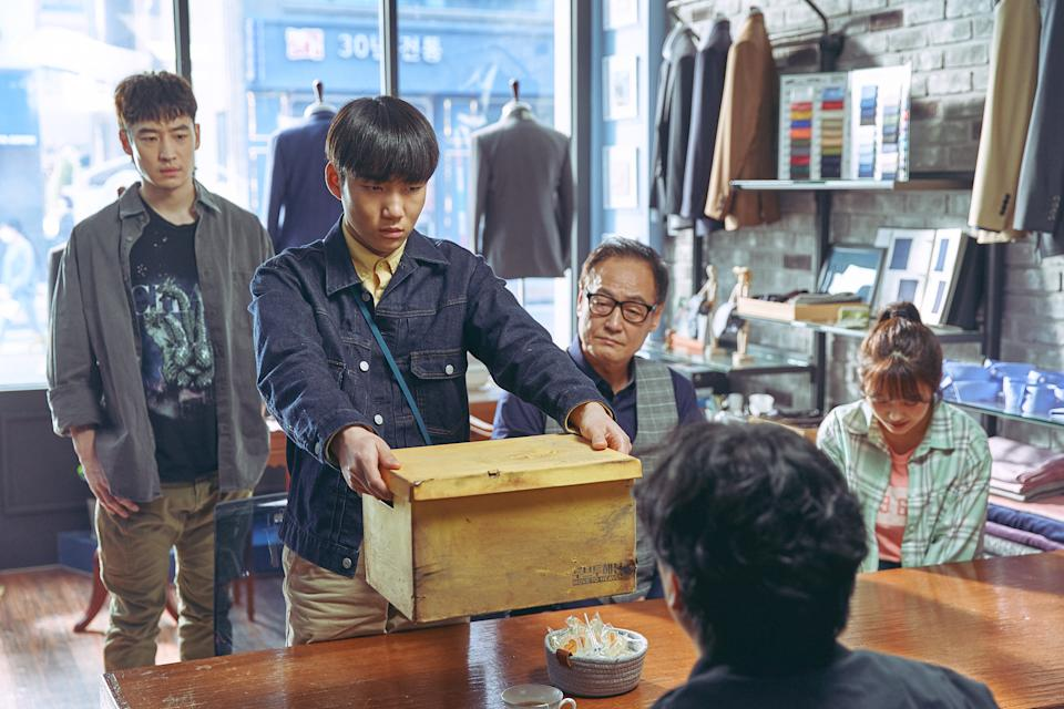 As Move To Heaven trauma cleaners, Geu-ru (Tang Jun-sang) and Sang-gu (Lee Je-hoon) clean up the belongings of the deceased and place them into yellow boxes. (Photo: Netflix)