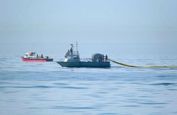PHOTO: A Marine Spill Response Corporation (MSRC) vessel, foreground, an oil spill removal organization (OSRO), deploys floating barriers known as booms to try to stop further incursion of an oil slick off Huntington Beach, Calif., Oct. 3, 2021. (Ringo Chiu/AP)