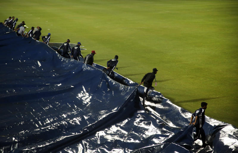 Groundsmen pull on the plastic sheets to uncover the field after the rain during the first Twenty20 cricket match between India and Sri Lanka in Gauhati, India, Sunday, Jan. 5, 2020. The match delayed for the rain. (AP Photo/Anupam Nath)