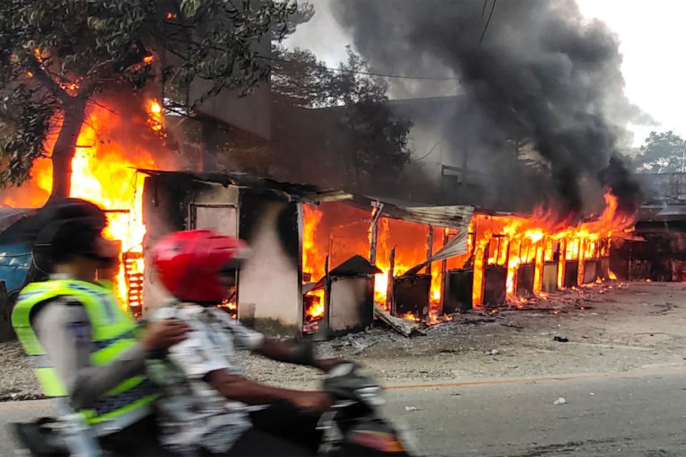 A motorist ride past a burning building after hundreds of demonstrators marched near Papua's biggest city Jayapura on August 29, 2019, where they set fire to a regional assembly building and hurled rocks at shops and hotels. Source: AFP