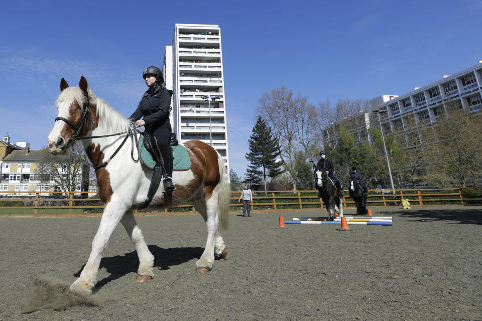 Manuela Jimenez, 15, rides Splash in a riding lesson at Ebony Horse Club in Brixton, south London, Sunday, April 18, 2021. In the midst of south London's hustle and bustle, only a 10-minute walk from a subway station, is a school where children are encouraged to horse around. The Ebony Horse Club provides 140 rides per week to children in the local community offering them the opportunity to learn important life skills along with horseback riding. (AP Photo/Kirsty Wigglesworth)