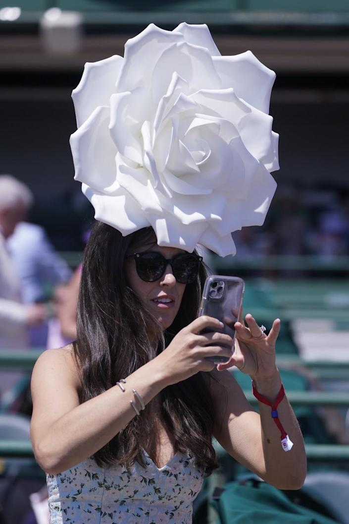 A woman takes a photo while wearing a large white rose-shaped hat.