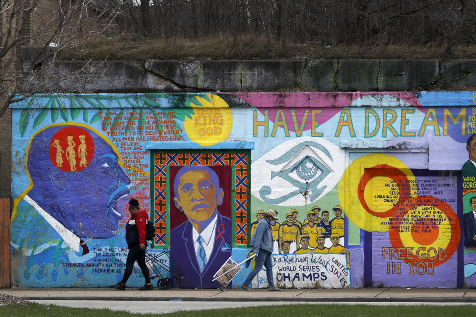 In this April 7, 2020, photo, two women pass each other and an African-American mural as they travel to and from a local grocery store on Chicago's Southside. As the coronavirus tightened its grip across the country, it is cutting a particularly devastating swath through an already vulnerable population, black Americans. (AP Photo/Charles Rex Arbogast)