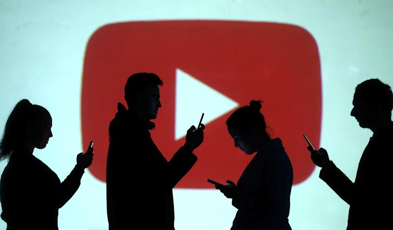 Silhouettes of mobile users are seen next to a screen projection of Youtube logo in this picture illustration