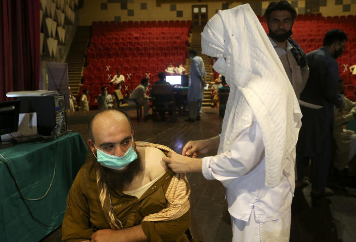 A government employee receives the Convidecia COVID-19 vaccine from a paramedic at a vaccination center in Nishtar hall, in Peshawar, Pakistan, Friday, June11, 2021. (AP Photo/Muhammad Sajjad)