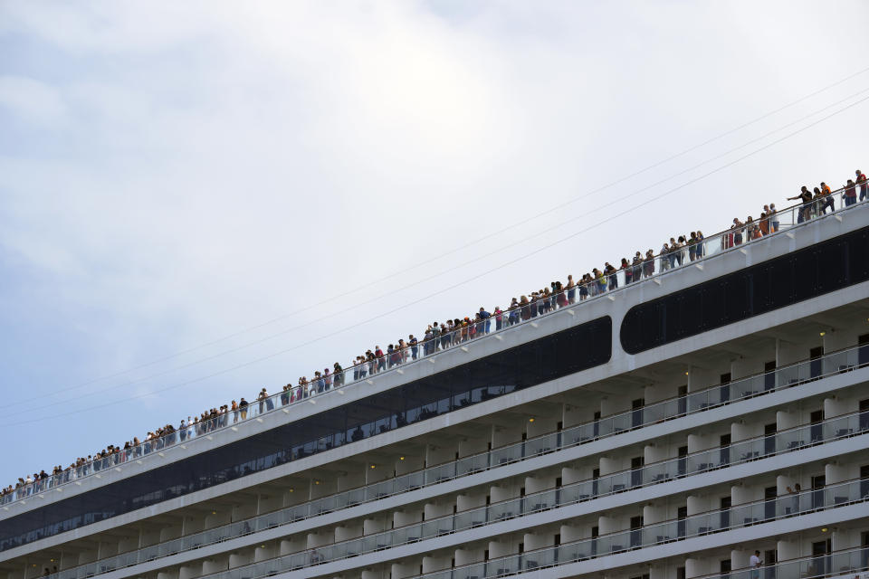 Passengers stand on the deck of the 92,409-ton,16-deck MSC Orchestra cruise ship as it departs from Venice, Italy, Saturday, June 5, 2021. The first cruise ship leaving Venice since the pandemic is set to depart Saturday amid protests by activists demanding that the enormous ships be permanently rerouted out the fragile lagoon, especially Giudecca Canal through the city's historic center, due to environmental and safety risks. (AP Photo/Antonio Calanni)