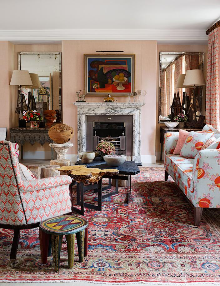 """<div class=""""caption""""> A Mark Gertler painting hangs over the drawing room's neoclassical mantel. Cocktail tables by <a href=""""https://tomstogdon.com/"""" rel=""""nofollow noopener"""" target=""""_blank"""" data-ylk=""""slk:Tom Stogdon"""" class=""""link rapid-noclick-resp"""">Tom Stogdon</a> for <a href=""""https://kitkemp.com/"""" rel=""""nofollow noopener"""" target=""""_blank"""" data-ylk=""""slk:Kit Kemp"""" class=""""link rapid-noclick-resp"""">Kit Kemp</a>; African side table; antique rug. </div> <cite class=""""credit"""">Simon Upton </cite>"""