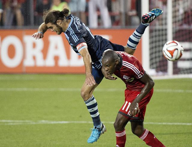 Toronto FC midfielder Jackson, right, battles for the ball against Sporting Kansas City's Graham Zusi, left, during second-half MLS soccer action in Toronto, Saturday, July 26, 2014. (AP Photo/The Canadian Press, Nathan Denette)