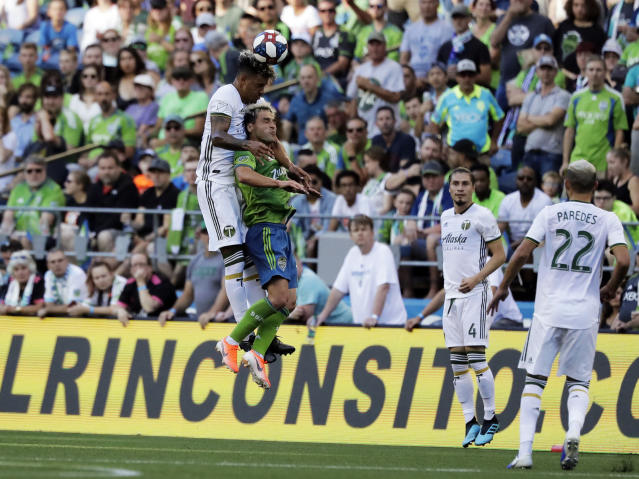 Portland Timbers defender Julio Cascante, left, heads the ball above Seattle Sounders forward Nicolas Lodeiro during the first half of an MLS soccer match, Sunday, July 21, 2019, in Seattle. (AP Photo/Ted S. Warren)