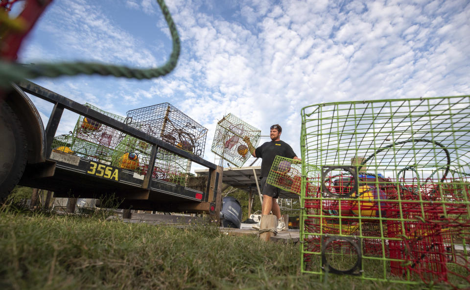 Crabber Thomas Fick Jr., of Vaucherie, loads some of his 250 crab traps he retrieved from water off Isle de Jean Charles in Terrebonne Parish, La., ahead of Hurricane Delta Wednesday, Oct. 7, 2020. (David Grunfeld/The Times-Picayune/The New Orleans Advocate via AP)