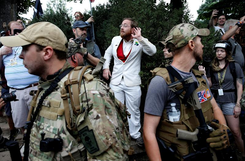 A white supremacist stands behind militia members after he scuffled with a counter-demonstrator.