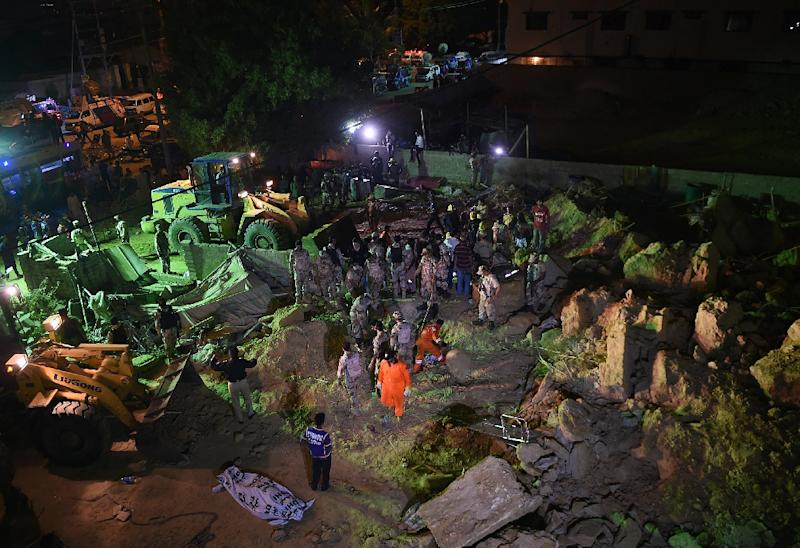 Pakistani soldiers and rescuers search for victims in the debris of a landslide in Karachi, on October 13, 2015 (AFP Photo/Asif Hassan)