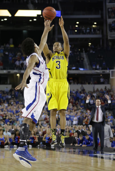 Michigan's Trey Burke (3) makes a three-point basket in the final seconds of the second half of a regional semifinal game against Kansas in the NCAA college basketball tournament, Friday, March 29, 2013, in Arlington, Texas. (AP Photo/David J. Phillip)