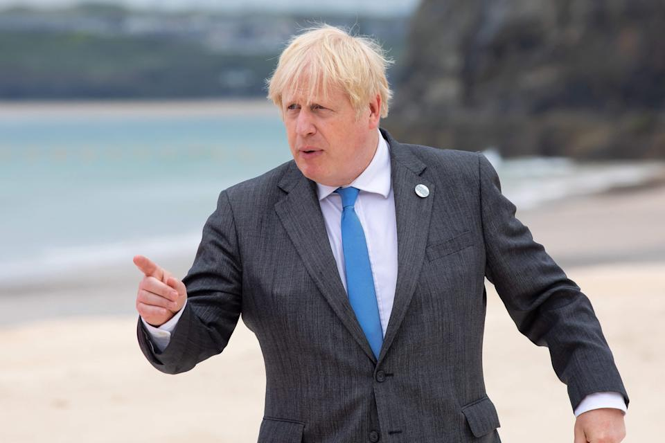 Britain's Prime Minister Boris Johnson gestures during the family photo at the start of the G7 summit in Carbis Bay, Cornwall on June 11, 2021. - G7 leaders from Canada, France, Germany, Italy, Japan, the UK and the United States meet this weekend for the first time in nearly two years, for three-day talks in Carbis Bay, Cornwall. - (Photo by Jonny Weeks / POOL / AFP) (Photo by JONNY WEEKS/POOL/AFP via Getty Images)