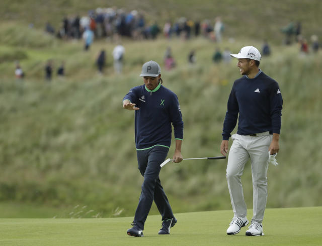 Rickie Fowler of the United States, left talks to Xander Schauffele of the United States as they walk to the 16th green during the third round of the British Open Golf Championships at Royal Portrush in Northern Ireland, Saturday, July 20, 2019.(AP Photo/Matt Dunham)