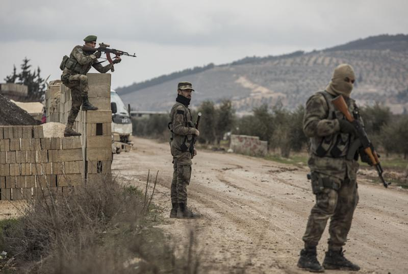 """Turkey-backed Free Syrian Army fighters secure an area where Turkish army's Operation Olive Branch continue in Azaz, northwestern Syria, Wednesday, Jan. 24, 2018. Turkish President Recep Tayyip Erdogan says Turkey's incursion into a Kurdish-held enclave in Syria is progressing """"successfully"""" and will continue until the last """"terrorist"""" is eliminated. (DHA-Depo Photos via AP)"""