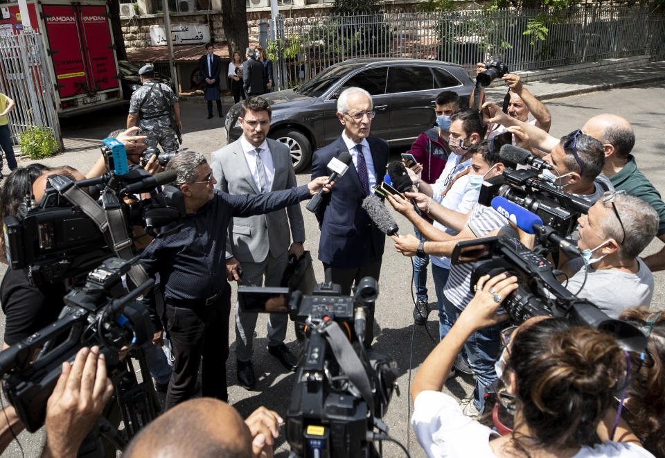 """Members of Carlos Ghosn's defense team, lawyer Jean Yves Le Borgne, center right, and Jean Tamalet, center left, speak with journalist outside the Justice Palace in Beirut, Lebanon, Friday, June 4, 2021. Lawyers of Ex-Nissan boss Carlos Ghosn said on Friday their client has answered hundreds of questions by French and Lebanese investigators over the past week describing him as """"happy and satisfied"""" to be given the opportunity to explain himself over accusations of financial misconduct. (AP Photo/Hassan Ammar)"""