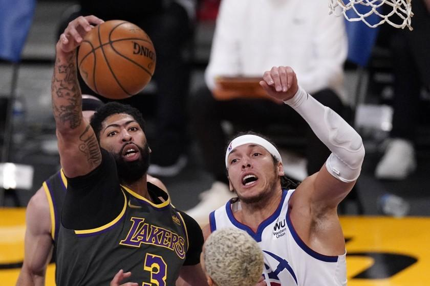 Los Angeles Lakers forward Anthony Davis, left, grabs a rebound away from Denver Nuggets forward Aaron Gordon during the first half of an NBA basketball game Monday, May 3, 2021, in Los Angeles. (AP Photo/Mark J. Terrill)