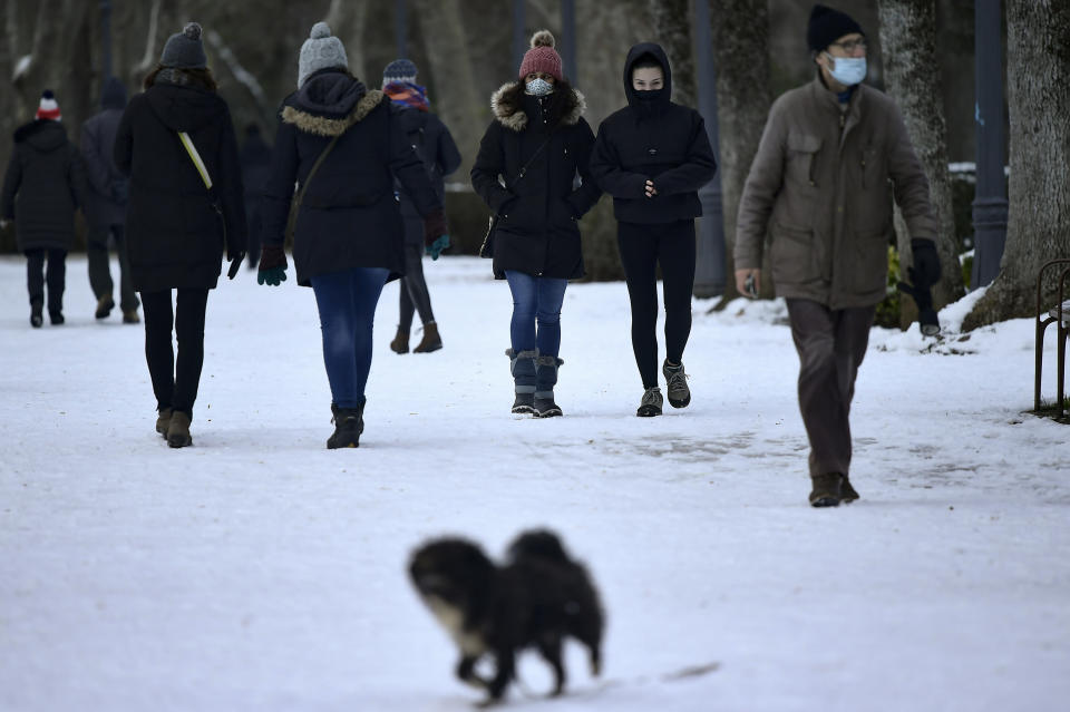 People protect themselves from the cold wind during frozen winter day, in Pamplona, northern Spain, Sunday, Jan. 10, 2021. A snow blizzard has blanketed large parts of Spain, impacting on traffic and all public transport services as the snow kept falling on Saturday. (AP Photo/Alvaro Barrientos)