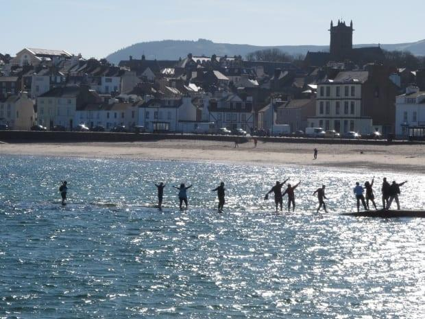 Beachgoers walk along a tidal causeway in the town of Peel on the Isle of Man on Monday, March 26, 2012. (Raphael Satter/Associated Press - image credit)