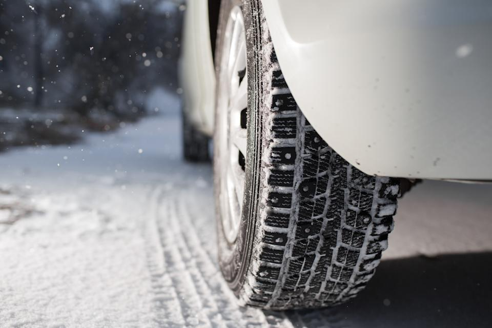 Closeup of car tires in winter. the first snow in late autumn.
