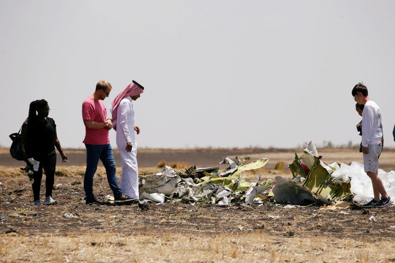 Family and friends of victims of the Ethiopian Airlines Flight ET 302 plane crash, look at debris after a commemoration ceremony at the scene of the crash, near the town of Bishoftu, southeast of Addis Ababa