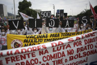 """Women simultaneously hold up placards with a message that reads in Portuguese; """"500K deaths! His fault!"""" during a demonstration against Brazilian President Jair Bolsonaro's handling of the coronavirus pandemic and economic policies protesters say harm the interests of the poor and working class, in Rio de Janeiro, Brazil, Saturday, June 19, 2021. Brazil is approaching an official COVID-19 death toll of 500,000 — second-highest in the world. (AP Photo/Bruna Prado)"""