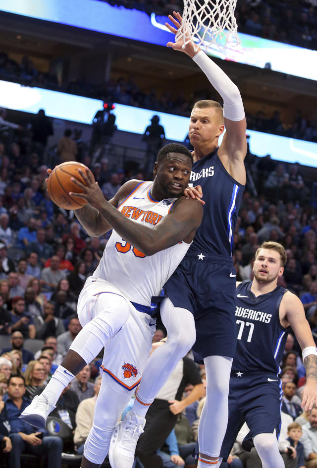 New York Knicks forward Julius Randle (30) looks to pass the ball under pressure from Dallas Mavericks forward Kristaps Porzingis (6) in the first half of an NBA basketball game Friday, Nov. 8, 2019, in Dallas. (AP Photo/Richard W. Rodriguez)
