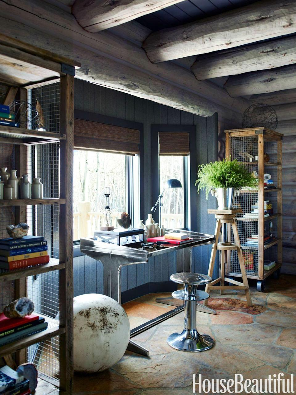 """<p>If your work space is cool, you may be more inclined to actually use it. A vintage aluminum desk and stool create an industrial vibe in this <a href=""""https://www.housebeautiful.com/design-inspiration/house-tours/g2928/thom-filicia-colorado-cabin/"""" rel=""""nofollow noopener"""" target=""""_blank"""" data-ylk=""""slk:Colorado cabin"""" class=""""link rapid-noclick-resp"""">Colorado cabin</a>'s study. Chicken-wire bookcases add a rustic touch to the room.</p>"""