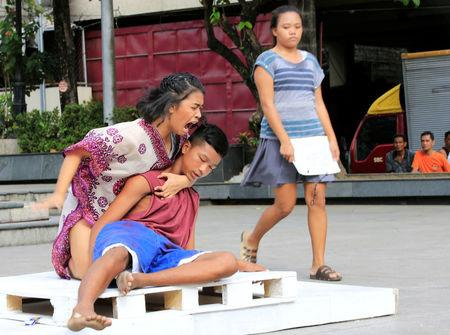 """Filipino theatre artists perform a """"La Pieta"""" scene during a short musical about the killings under the Philippine government's anti-drug campaign, in Pandacan city"""