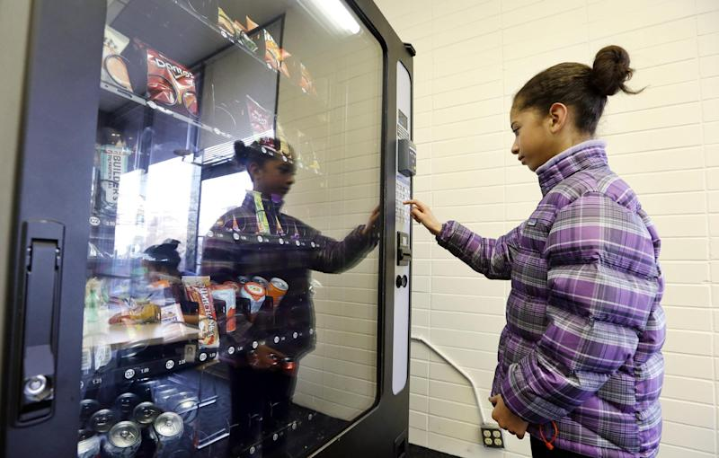 In this Dec. 23, 2013 photo, a 12-year-old girl, who declined to be identified, makes a purchase at a vending machine in Seattle. Office workers in search of snacks will be counting calories along with their change under new labeling regulations for vending machines included in President Barack Obama's health care overhaul law. The Food and Drug Administration, which is expected to release final rules early next year, says requiring calorie information to be displayed on roughly 5 million vending machines nationwide will help consumers make healthier choices. (AP Photo/Elaine Thompson)