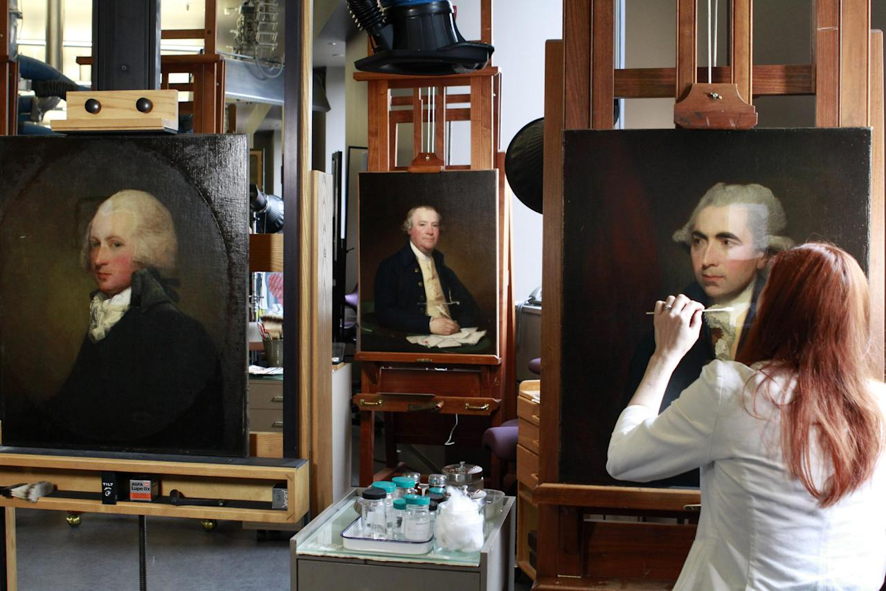 In this photo taken Monday, June 18, 2012, painting conservator Joanna Dunn removes varnish, which had yellowed with age, as she restores a Gilbert Stuart painting of Luke White at the National Gallery of Art's Painting Conservation Lab in Washington. (AP Photo/Jacquelyn Martin)