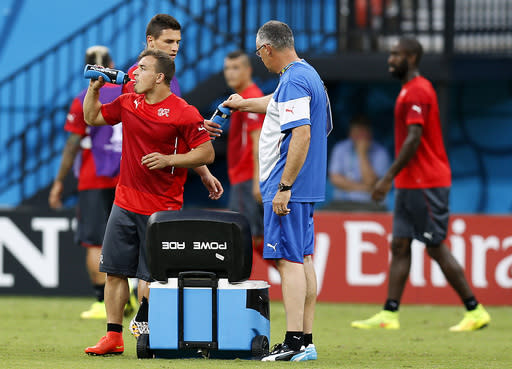 Switzerland's Xherdan Shaqiri, left, refreshes during a training session at the Arena da Amazonia in Manaus, Brazil, Tuesday, June 24, 2014, one day before the group E match between Honduras and Switzerland of the 2014 soccer World Cup. (AP Photo/Frank Augstein)