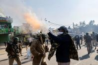 A police officer fires tear gas to stop farmers opposing the newly passed farm bills from entering the national capital Delhi, at Singhu border, India