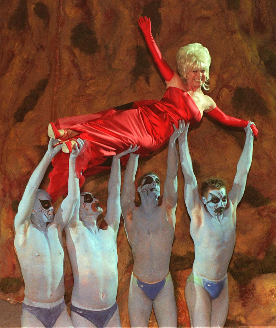 Eastenders star Barbara Windsor is held aloft during a celebrity fashion show to launch the premiere of the new Walt Disney film 'A Bug's Life', at the Commonwealth Institute, Kensington in London. (Photo by Rosie Hallam - PA Images/PA Images via Getty Images)