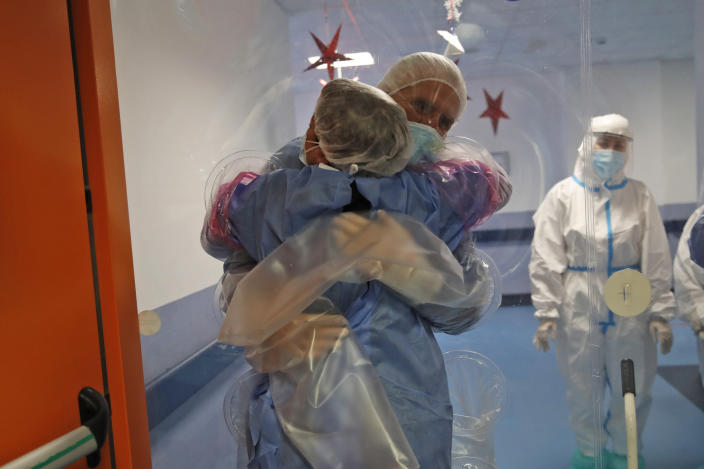 Ela Gubbiotti hugs her partner Giancarlo Vannimartini, an anesthesiologist who has been hospitalized for 10 days, in a safe room where patients and relatives can hug each other protected by a plastic film screen set up inside the COVID-19 ward of the Ospedale dei Castelli Hospital in Ariccia, near Rome, Wednesday, Jan. 20, 2021. (AP Photo/Alessandra Tarantino)