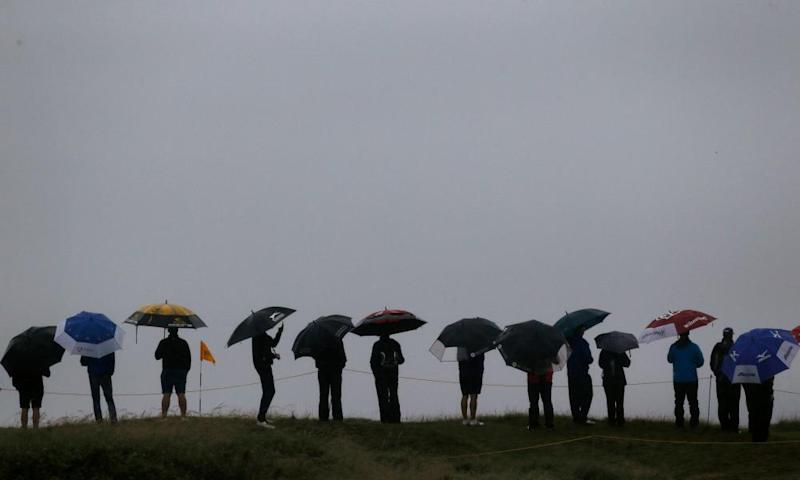 Spectators shelter under umbrellas due to heavy rain at the Open Championship at Royal Troon Golf Club, South Ayrshire, in July 2016
