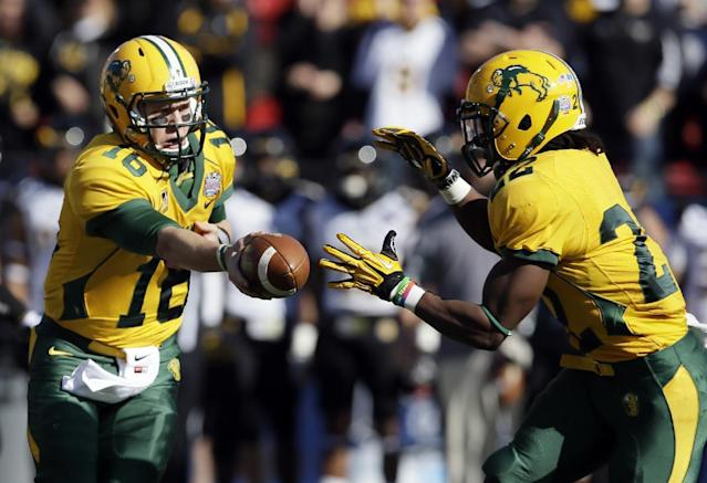 North Dakota State quarterback Brock Jensen (16) hands the ball off to running back Sam Ojuri (22) in the first half of the FCS championship NCAA college football game against Towson, Saturday, Jan. 4, 2014, in Frisco, Texas. (AP Photo/Tony Gutierrez)