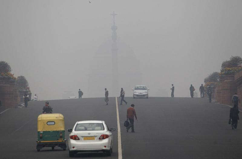 Smog and fog envelop the Indian Presidential Palace, behind, as commuters cross a street in the morning in New Delhi, India, Wednesday, Feb. 5, 2014. On bad days in India's congested capital, the air is so murky it slows traffic to a crawl because visibility is so poor. Conversations are punctuated with rasping coughs. Weak bands of sunlight filter through a grainy sky. (AP Photo/Tsering Topgyal)