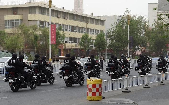 Armed police patrol on motorbikes along a street in Hotan, China's western Xinjiang region, on April 16, 2015 (AFP Photo/Greg Baker)