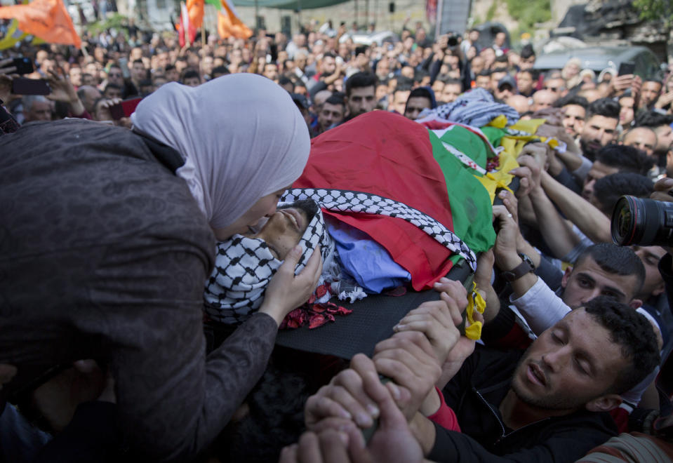 FILE - In this March 21, 2019 file photo, Wafa Manasra, mother of Palestinian Ahmad Manasra, kisses him goodbye during his funeral in the West Bank village of Wad Fokin, near Bethlehem. In August 2020, Israeli military prosecutors offered three months of community service to a soldier who shot and killed Manasra, an unarmed Palestinian man who exited his vehicle to assist a second motorist who had also been shot -- in a case that has drawn renewed attention to a justice system that Palestinians and human rights activists say has created an atmosphere of impunity. The deal is now being reviewed by the Israeli Supreme Court. (AP Photo/Nasser Nasser, File)