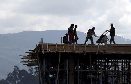 Construction workers work on the roof of a new building at the Mercato market in Addis Ababa