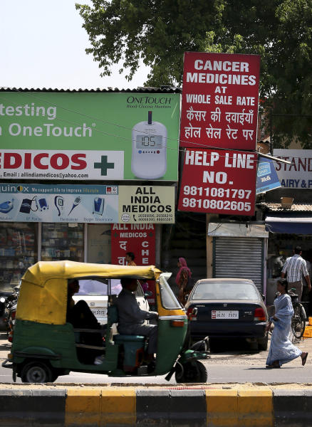 A billboard for wholesale rate of cancer medicines is seen outside a chemist store, in New Delhi, India, Monday, April 1, 2013. India's Supreme Court on Monday rejected drug maker Novartis AG's attempt to patent a new version of a cancer drug Glivec in a landmark decision that healthcare activists say ensures poor patients around the world will get continued access to cheap versions of lifesaving medicines. (AP Photo/Manish Swarup)
