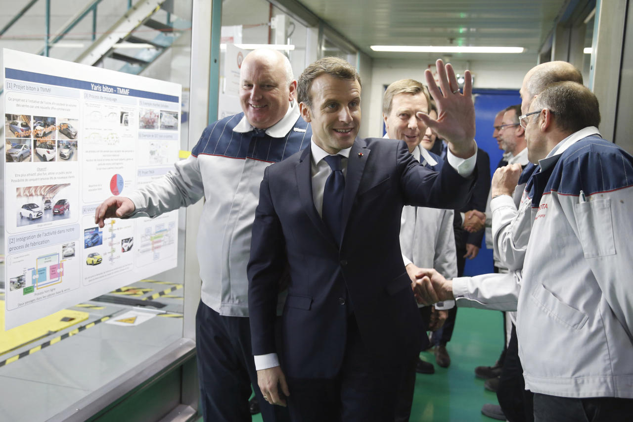 <p> French President Emmanuel Macron waves as he visits Toyota's automobile manufacturing plant with Director Luciano Biondo, left, in Onnaing, northern France, Monday, Jan. 22, 2018. (Pascal Rossignol/Pool Photo via AP) </p>