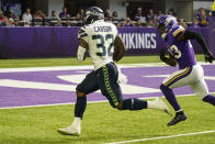 Seattle Seahawks running back Chris Carson (32) heads to the end zone for a touchdown past Minnesota Vikings free safety Xavier Woods (23) in the first half of an NFL football game in Minneapolis, Sunday, Sept. 26, 2021. (AP Photo/Jim Mone)
