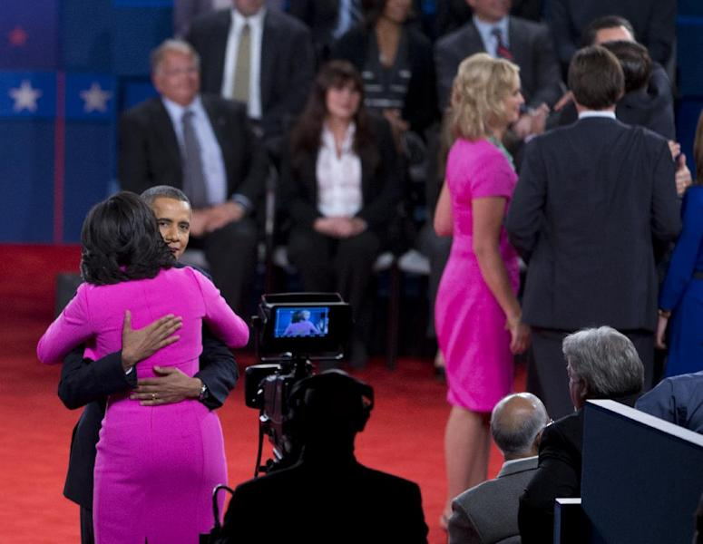 FILE - This Oct. 16, 2012 file photo shows President Barack Obama embracing first lady Michelle Obama on stage after presidential debate at Hofstra University in Hempstead, N.Y. Every year fashion offers up the good, the bad and the ugly. But what the industry is really built on _ and consumers respond to _ is buzz. The wives of the presidential candidates turned out to the second debate between Barack Obama and Mitt Romney in practically the same shade of hot pink. But they weren't by the same designer: Ann Romney's was by Oscar de la Renta, and Obama's by Michael Kors. (AP Photo/Carolyn Kaster)
