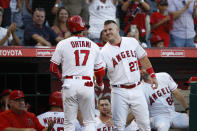 Los Angeles Angels' Shohei Ohtani shakes hands with Mike Trout after hitting a home run during the first inning of a baseball game against the Seattle Mariners, Saturday, Sept. 15, 2018, in Anaheim, Calif. (AP Photo/Jae C. Hong)
